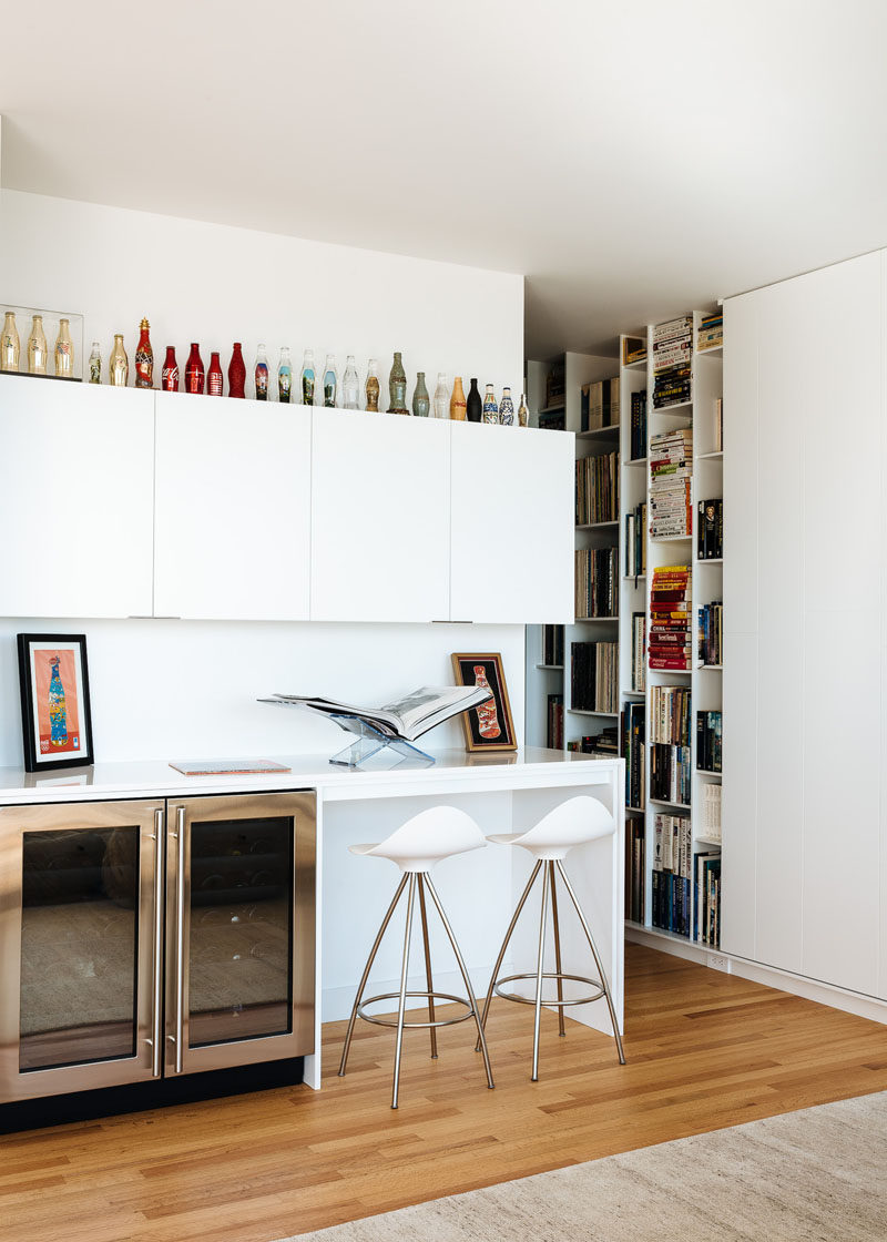 This modern bar area has a couple of drink fridges and cabinets for storage. The home owners Coca-Cola bottle collection sits on top of the cabinets and stands out against the white walls. #WhiteCabinetry #Bar