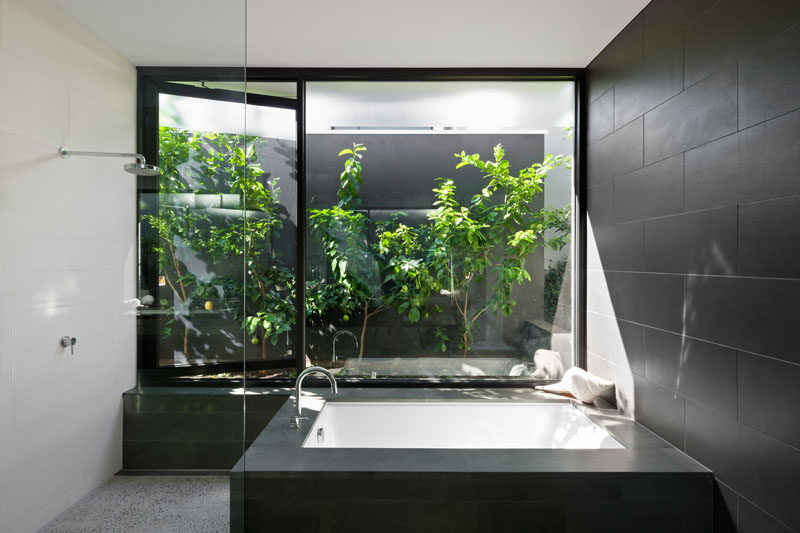 In this modern bathroom, there's a built-in bathtub that sits beside the shower. A window that opens to the garden makes it feel like you're showering outside. #ModernBathroom #BuiltInBathtub #Windows