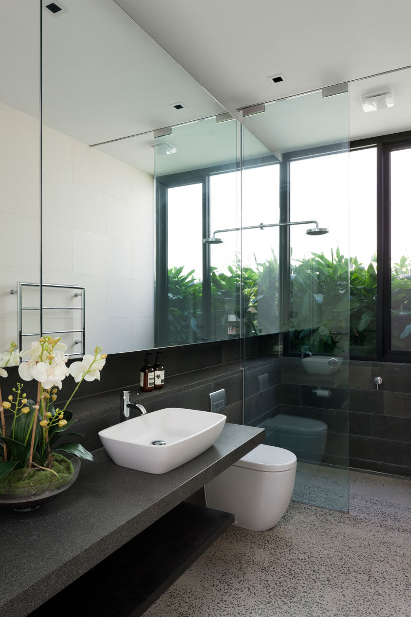 In this modern bathroom, a large window travels through from the vanity area to the shower, helping to reflect light throughout the space. #ModernBathroom #BathroomMirror