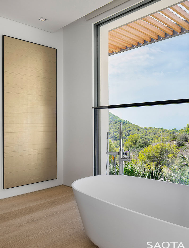 In this simple and modern bathroom, a freestanding bathtub is located in front of the window to take advantage of the views. #ModernBathroom