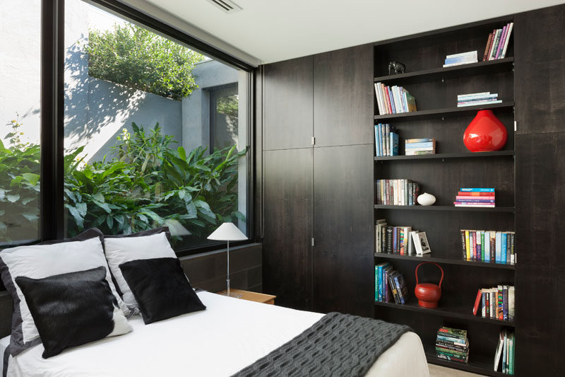 In this modern bedroom, dark wood shelving and closets line the wall, while large windows provide a glimpse of the lush plants outside. #ModernBedroom #Shelving #Windows