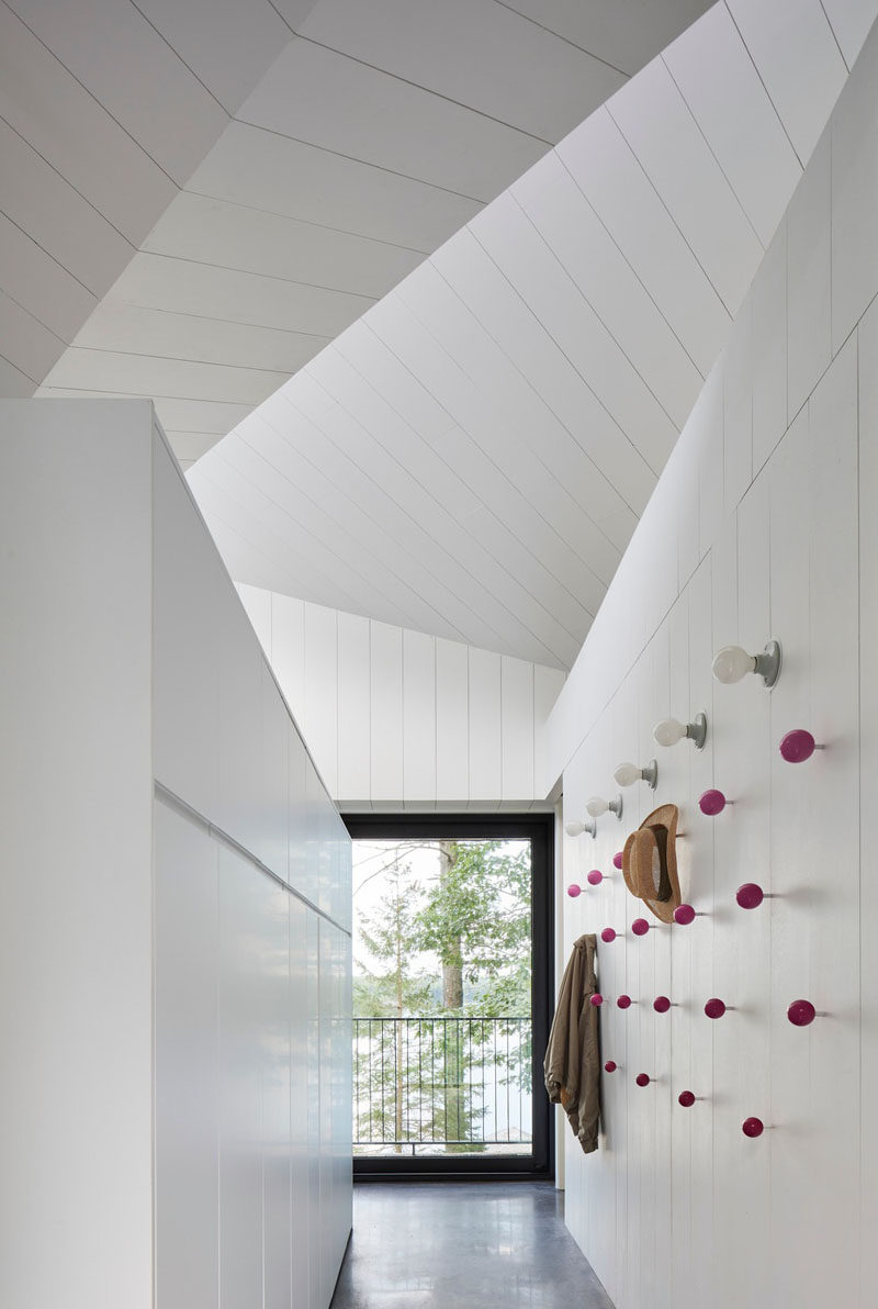 This modern house has small hallway by the front door with closets and on the wall, there's pink push-pin-like wall hooks and a row of lighting. #WallHooks #Decor #Entryway