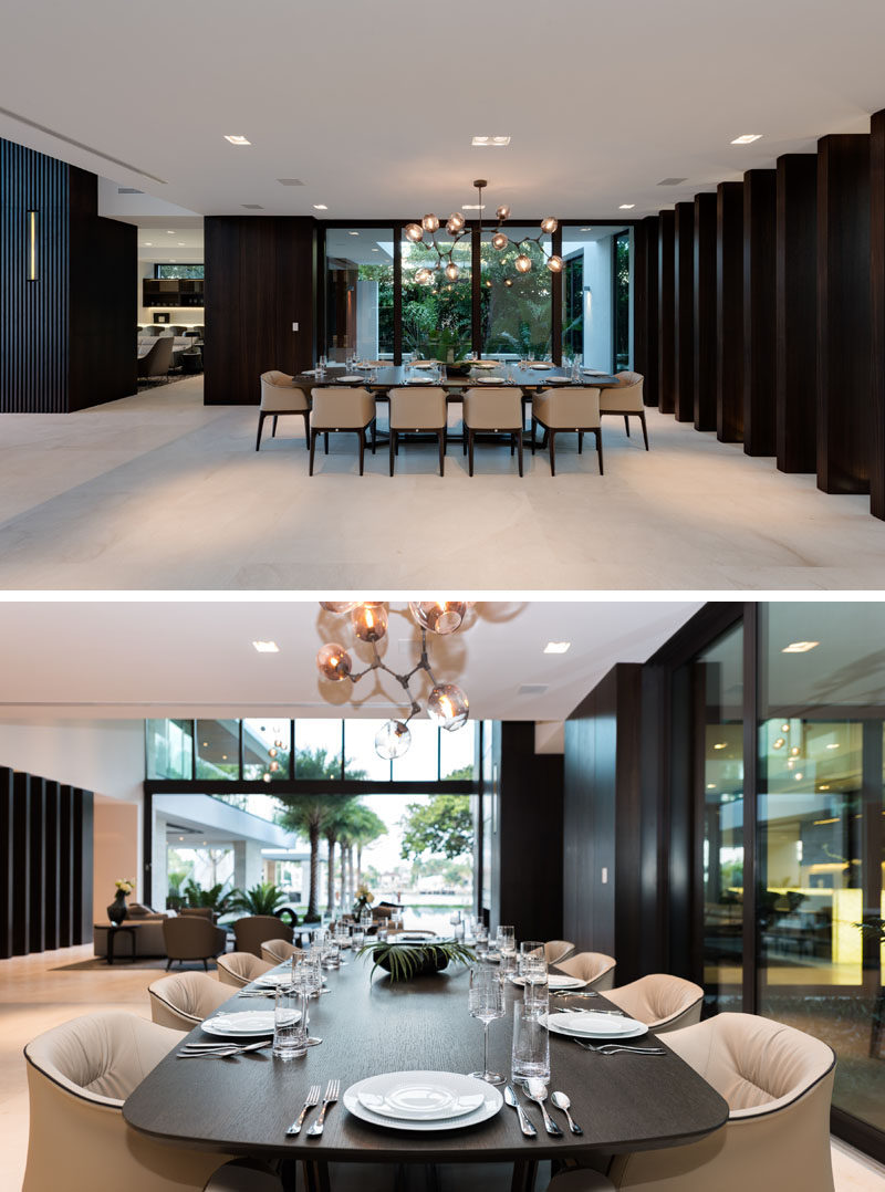 This formal dining area has views of a water feature outside. #FormalDiningRoom #ModernDiningRoom