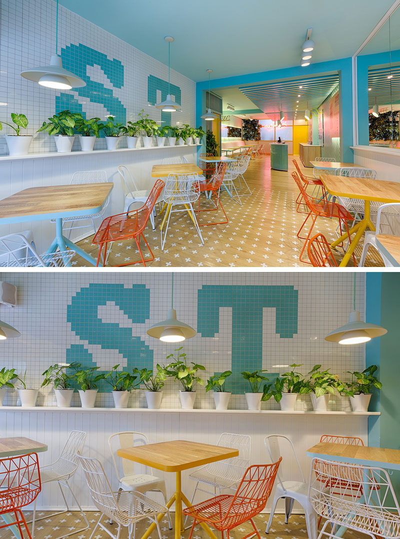 At the front of this modern ice cream store, there's a tiled wall with plants on one side, and on the opposite wall, there's mirrors that help to make the space feel larger. #IceCreamStore #RetailDesign