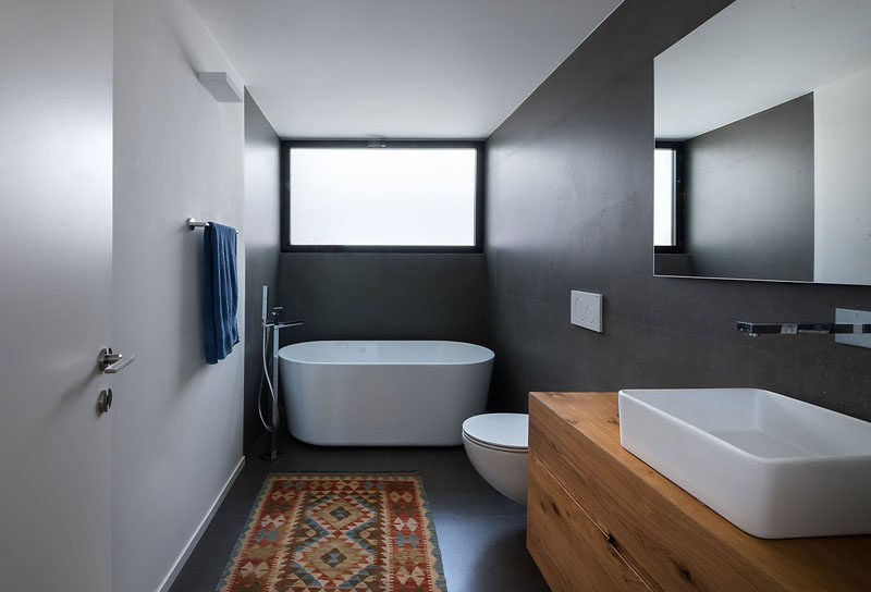 In this bathroom, grey walls and floors have been combined with a white freestanding bathtub and a large wood vanity to create a modern look. #ModernBathroom #BathroomDesign