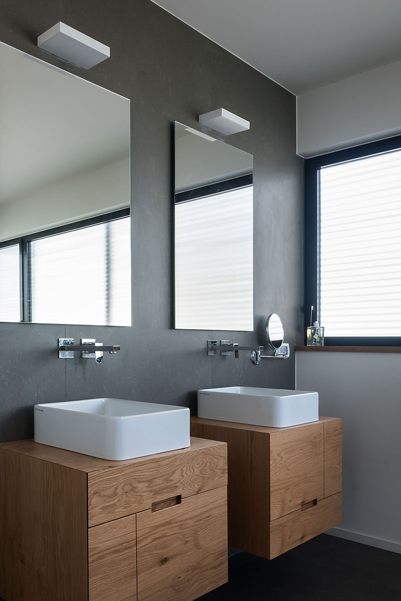 In this bathroom, grey walls and floors have been combined with a white sinks and two wall-mounted wood vanities to create a modern look. #ModernBathroom #ModernWoodVanity