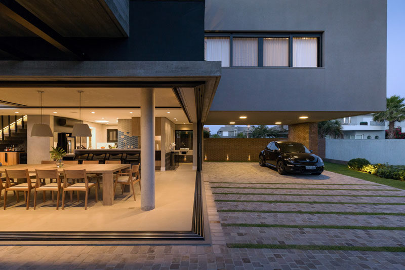 Sliding glass walls open up the dining room and interior of this modern house the driveway and carport. #GlassWalls #Carport #Driveway