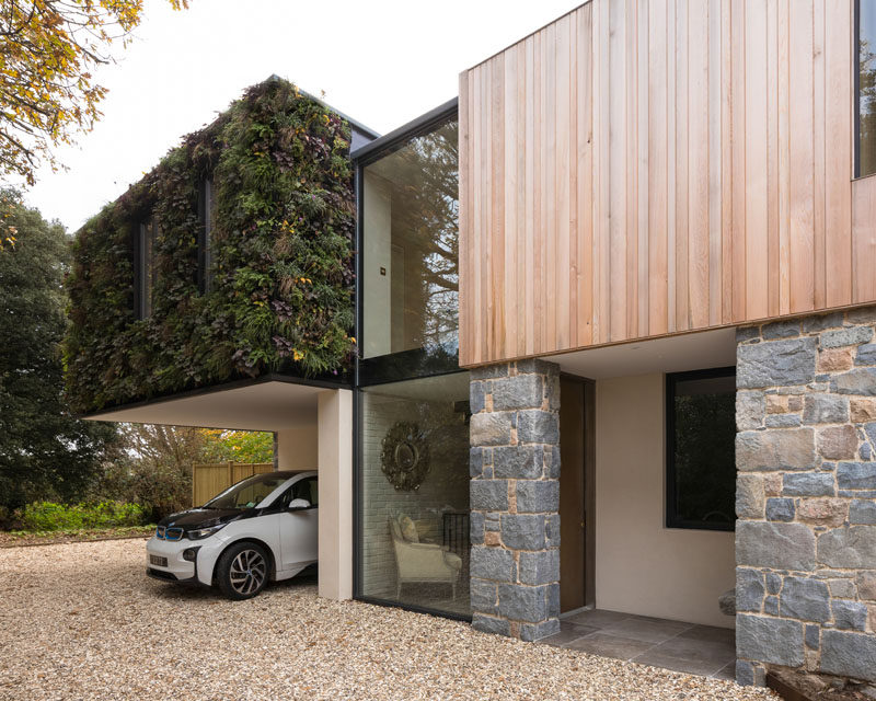 This modern house is covered in granite and cedar, while a living green wall adds a natural touch to the exterior. #Cedar #Granite #GreenWall #ModernArchitecture