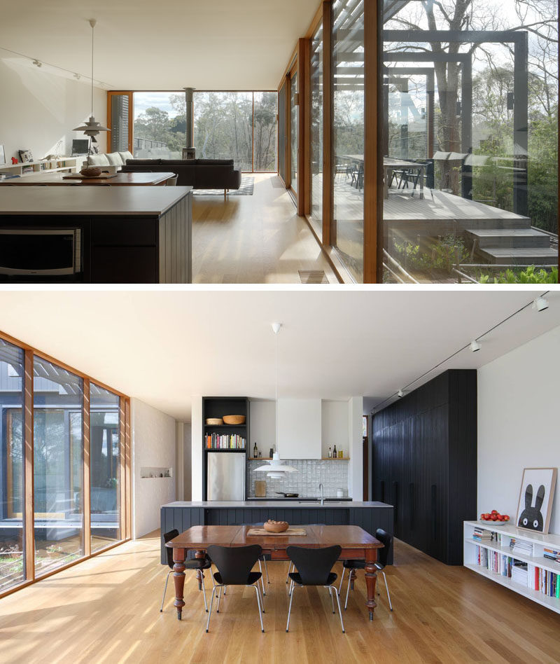 Inside this modern house extension, there's a new living room, dining area and kitchen, that all feature white walls, American oak floors with an oil finish and cedar windows. Black cabinets in the kitchen tie in with the black exterior of the extension. #BlackKitchen #OpenFloorPlan #HouseExtension