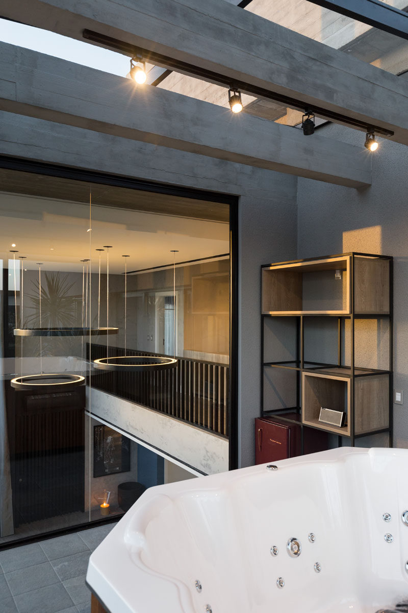 This modern house has a hot tub room that overlooks the living room through its floor-to-ceiling window. #HotTub #Windows