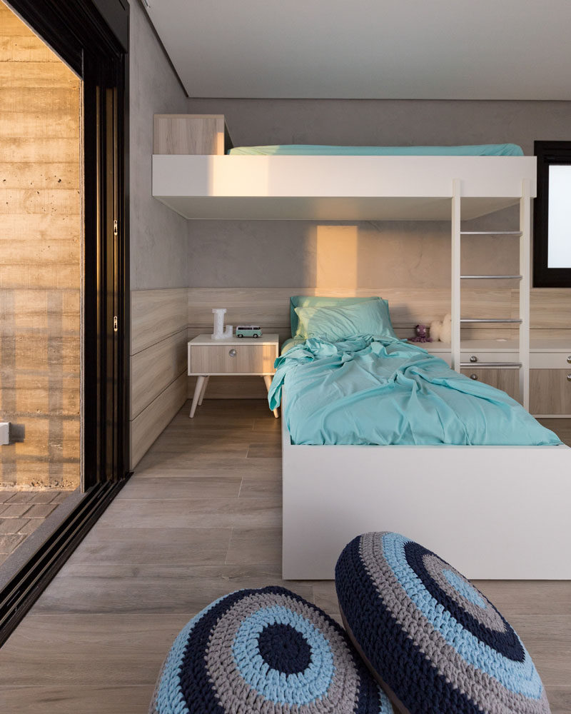 This modern children's bedroom has a couple of beds, one of which is a loft bed. #LoftBed #KidsBedroom