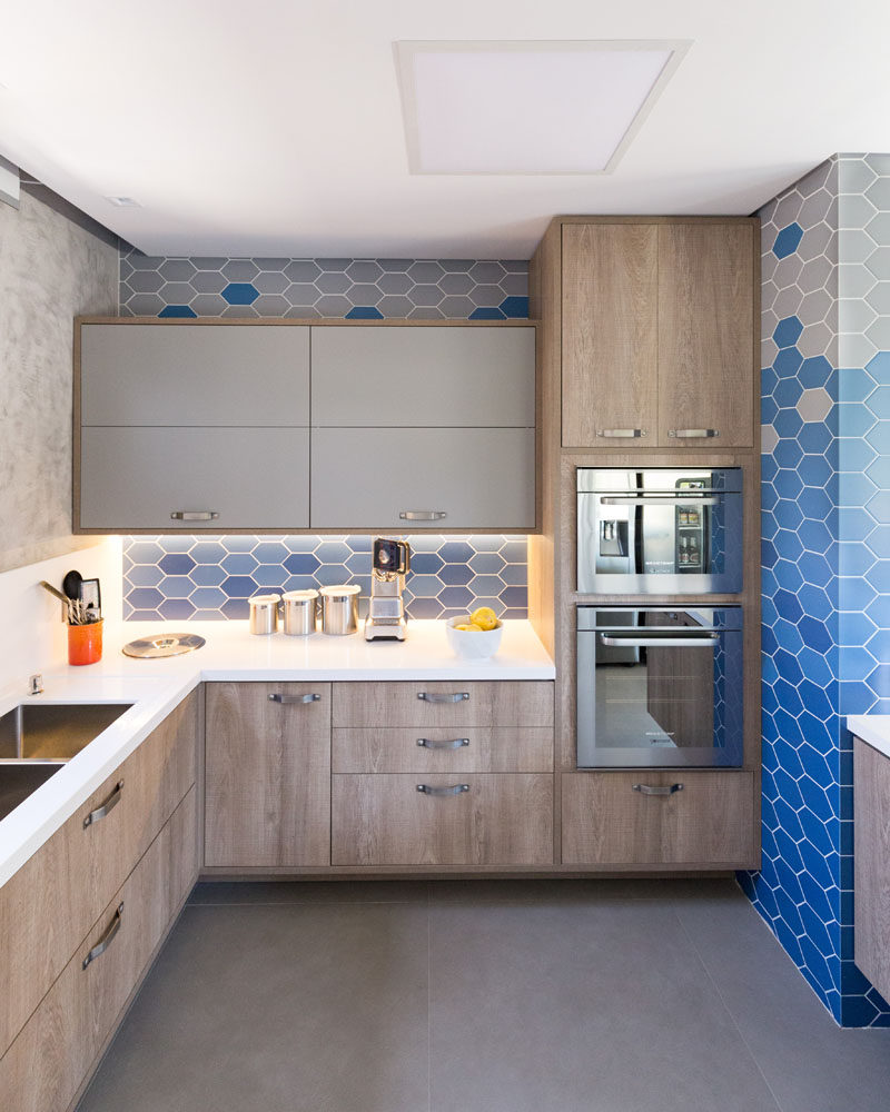 In this modern kitchen, hexagonal blue and light grey tiles cover the walls, while light wood and grey cabinets are combined with a white countertop to keep tings bright. #ModernKitchen #HexagonalTiles