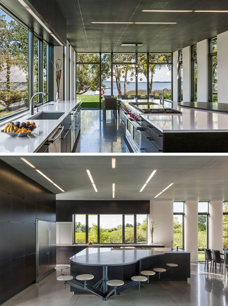 In this modern kitchen, there's concrete floors with radiant heat, and on the ceiling there's perforated blackened steel. To make sure there's enough room for the family in the kitchen, custom designed stools have been attached to the large curved island. #IndustrialModern #KitchenDesign