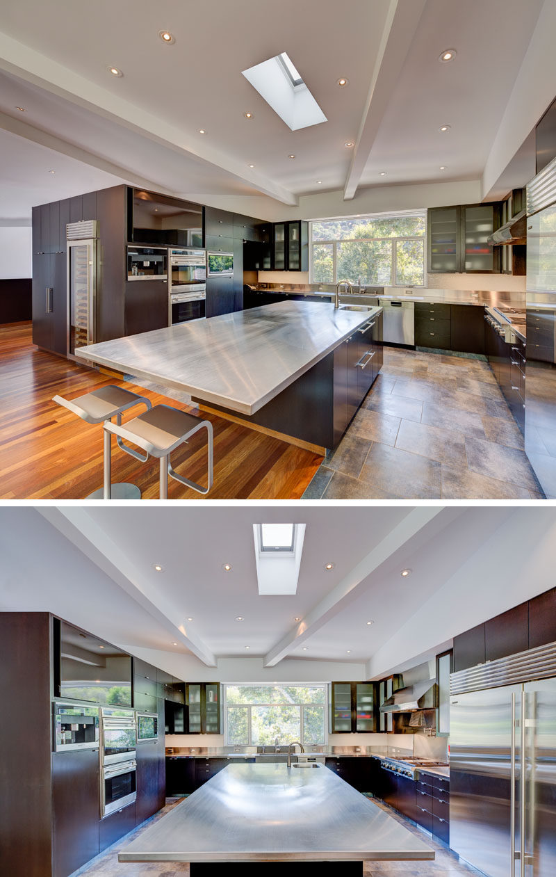 In this modern and expansive kitchen, there's a large island centrally located in the U-shaped kitchen, while windows above the sink and a skylight add natural light to the space. #KitchenDesign #KitchenIsland