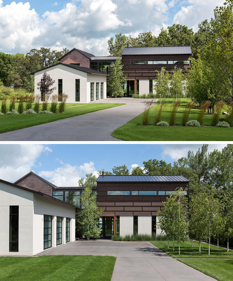 This industrial modern house, which is located next to a grove of 200 year old oak trees, has a landscaped front years with a driveway that leads to a garage. #IndustrialModern #HouseDesign #Driveway