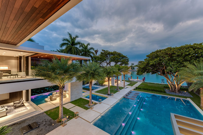 A modern landscaped backyard with water features, an infinity edge swimming pool, an outdoor kitchen and a private dock.