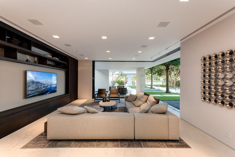 This modern living room has living room that has sliding glass doors that pocket and disappear, helping to blur the line between indoor and outdoor living. #PocketDoors #SlidingGlassWalls #LivingRoom