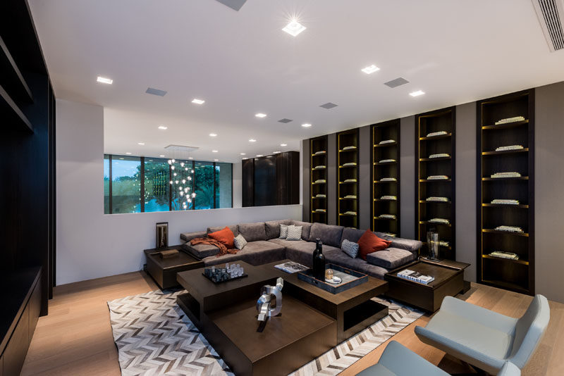 A modern living room with an L-shaped couch and a wall of dark wood built-in shelving.
