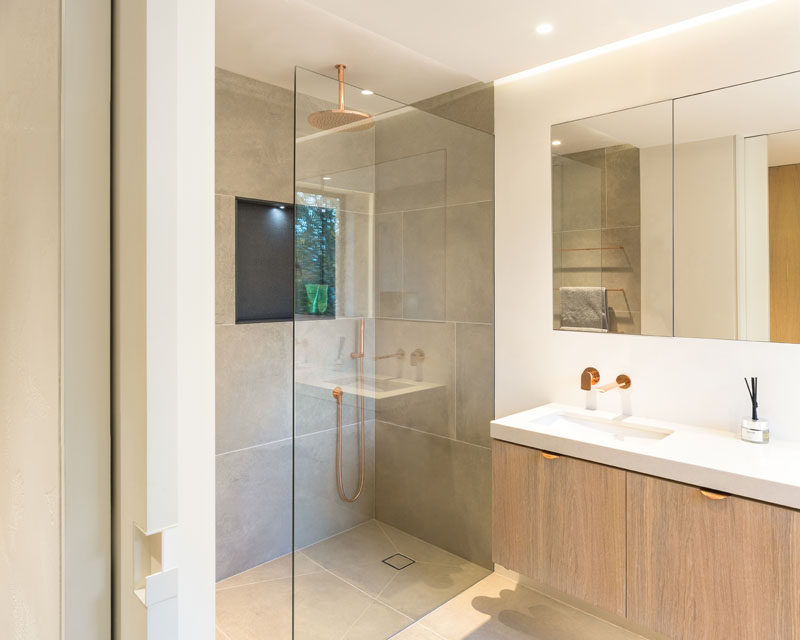 In this master ensuite bathroom, there's a walk-in shower with a rainfall showerhead, and above the mirror on the wall there's hidden lighting to create a calm ambiance. #ModernBathroom #EnsuiteBathroom