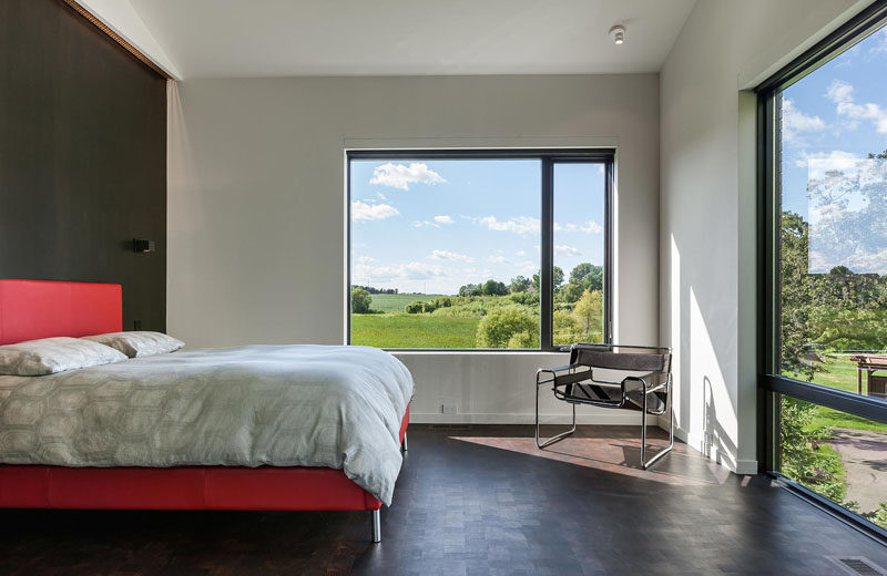 In this master bedroom, large windows provide views of the trees and the surrounding landscape. #MasterBedroom #Windows