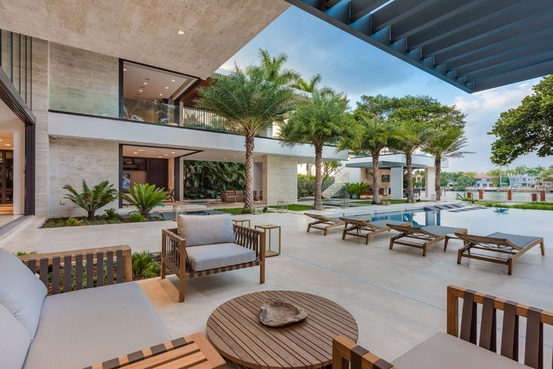 In the backyard of this modern house, there's a covered outdoor lounge, a large grassy area, more than 100 feet of dock space, an outdoor kitchen and cabana with rooftop access. #Landscaping #OutdoorLounge