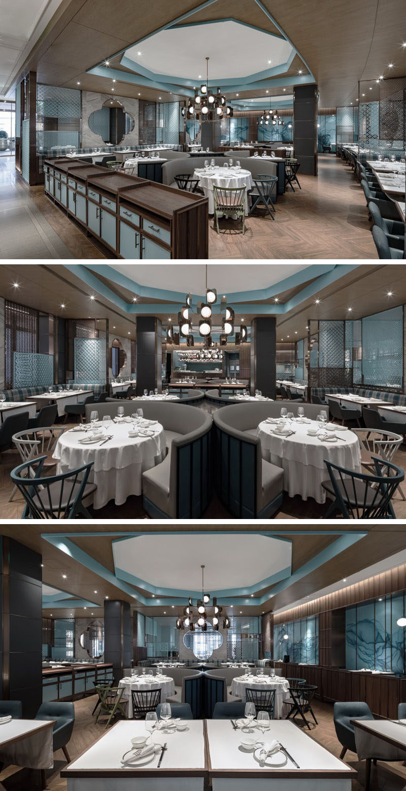 In the main dining area of this modern restaurant, a decagon ceiling feature and chandelier are positioned above curved seating booths. #RestaurantInterior #ModernRestaurant