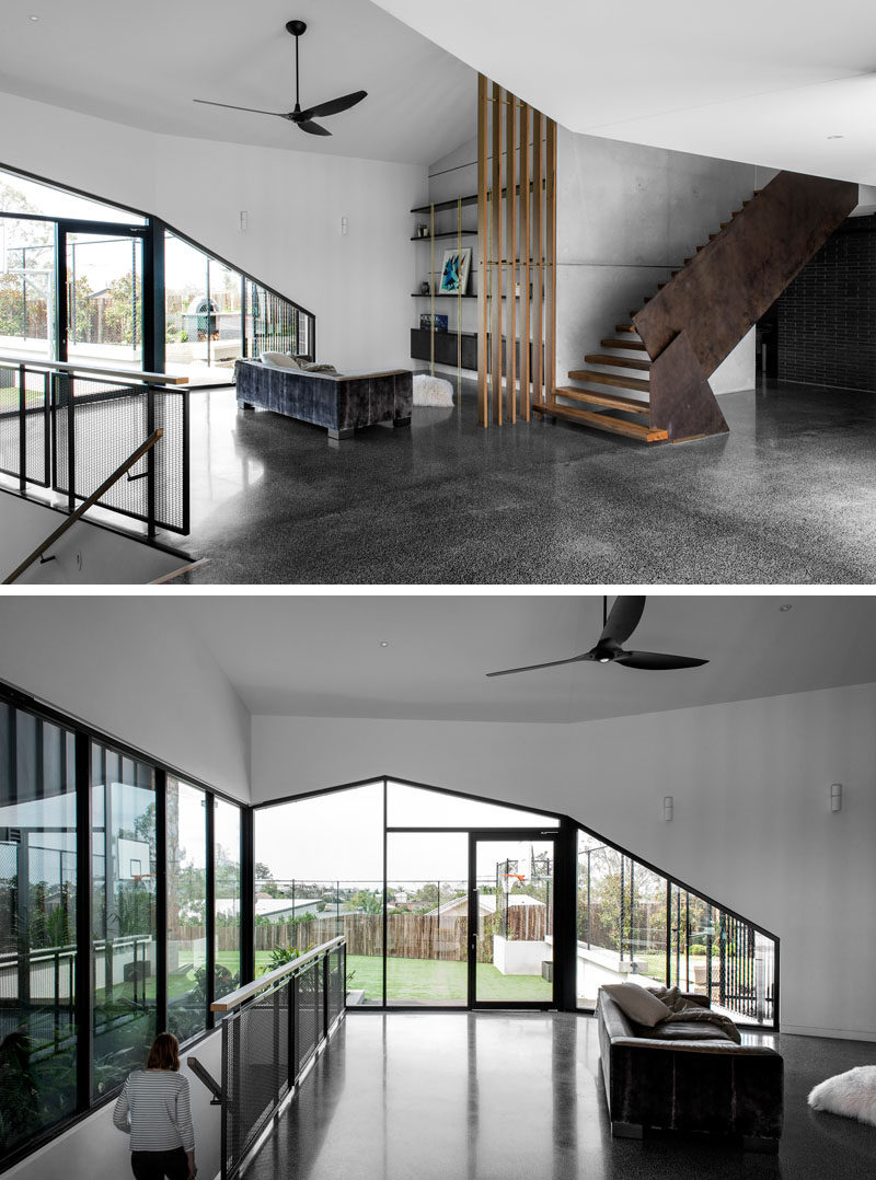 This modern house has an open entryway with a sitting / reading area with shelving against the wall. #SittingArea #Entryway #Windows