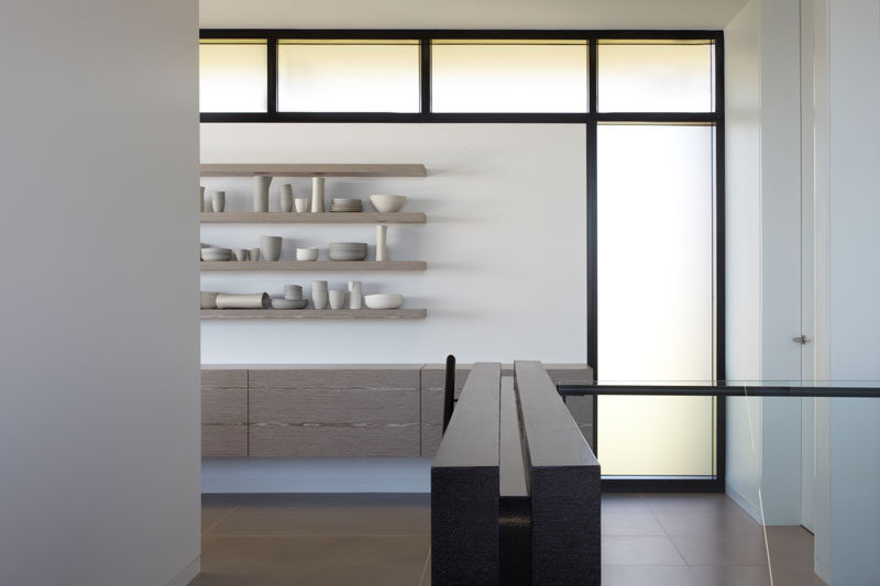 This modern house has windows that wrap around open shelving and a floating storage cabinet. #Windows #Shelving