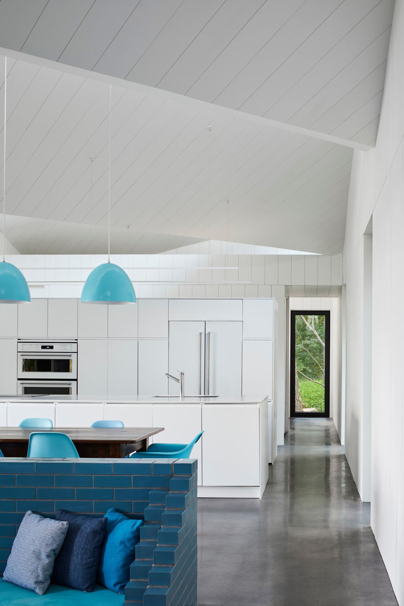 Stepping inside this modern house, the interior is fun and welcoming, with bright white walls and ceilings, a polished concrete floor with turquoise furnishings and design elements. #WhiteInterior #BlueFurniture #WhiteAndBlueInterior