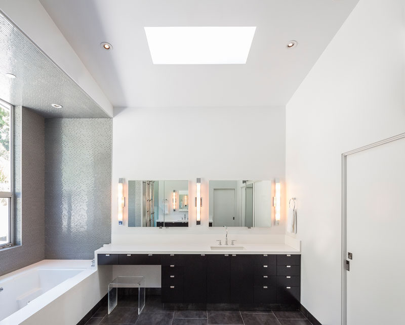 In this modern and minimal bathroom, a black vanity is topped with a white countertop that matches the walls, ceiling and bath.#Bathroom #ModernBathroom