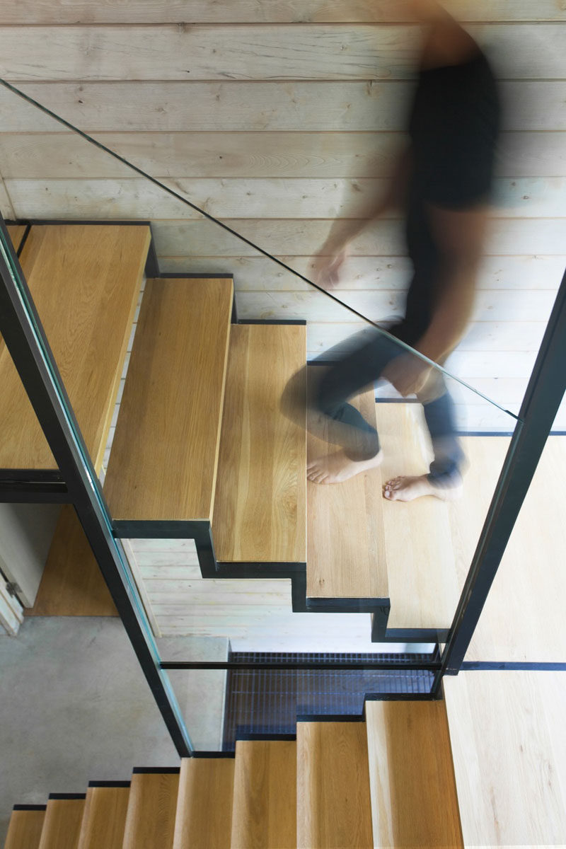 Wood and steel stairs with a glass handrail lead to the second floor of this modern vacation house. #ModernStairs #StairDesign #WoodAndSteel
