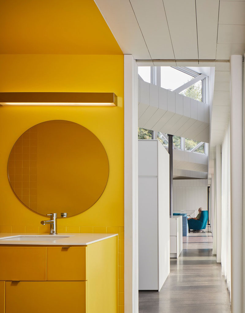 This modern house has a bright yellow bathroom that stands from the mostly white interior. #YellowBathroom #ModernBathroom