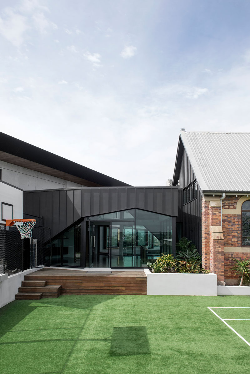 This modern house that connects with a renovated church has an an outdoor space with a tennis court and basketball hoop #ModernLandscaping #Architecture