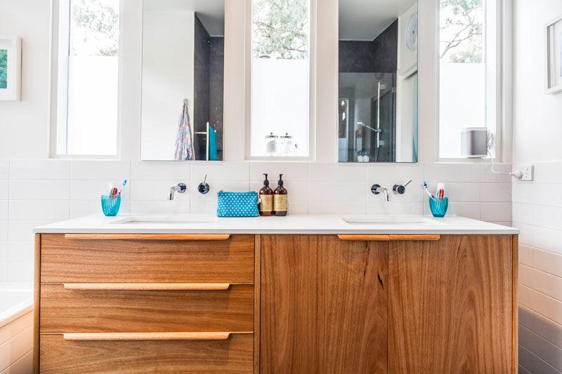 This mid-century modern inspired master bathroom has a bespoke wood vanity with handmade handles/pulls. #Bathroom #WoodVanity