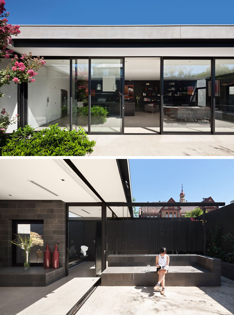 Sliding glass doors open the interior spaces of this modern house to a private courtyard filled with plants and seating. #GlassWall #ModernHouse #Courtyard