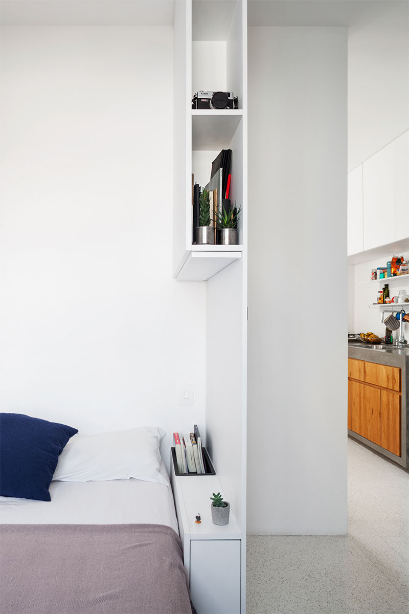 Simple shelving in this modern bedroom provides extra storage, and acts as a bedside table and privacy wall. #Bedroom #Shelving