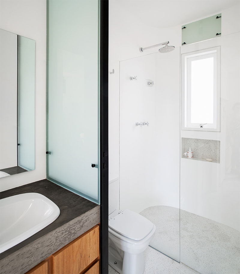 This small bathroom has a wood and concrete vanity and a walk-in shower. #SmallBathroom #BathroomDesign