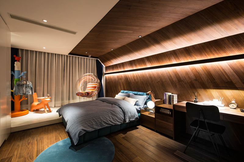 This modern kids bedroom features unique wrap-around wood accent wall with hidden lighting, that continues onto the ceiling. #AccentWall #ModernBedroom #WoodHeadboard