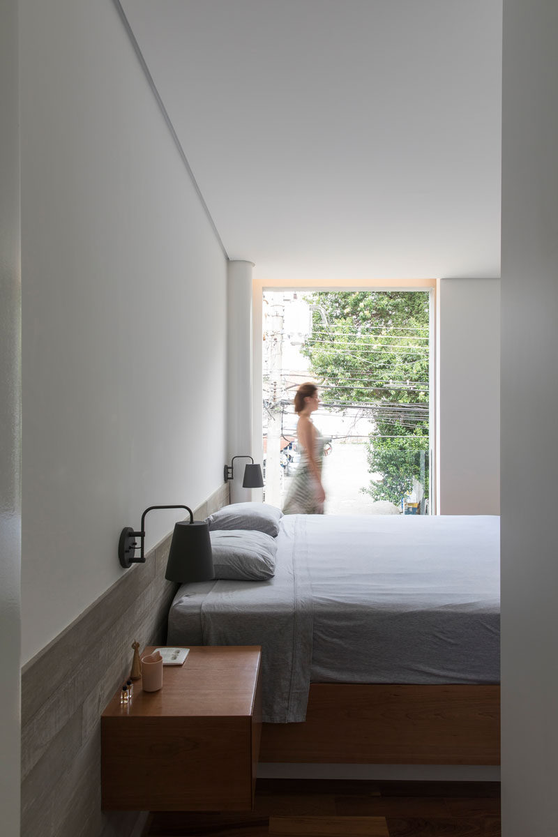 This simple bedroom has a floor-to-ceiling window that overlooks the street. A wood shutter can be closed to provide privacy for the bedroom. #Bedroom #Window
