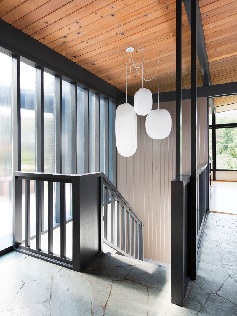 In this mid-century modern remodel, a black staircase leads down to the lower floor of the home. #BlackStairs
