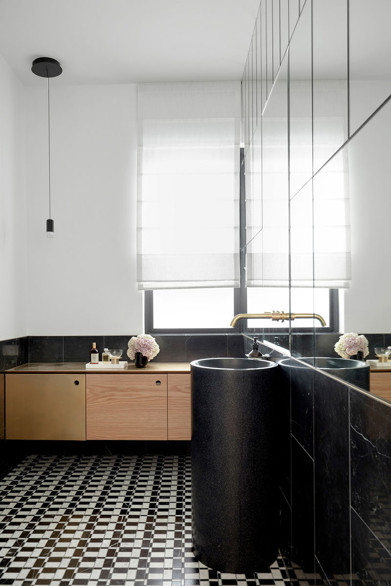 In this contemporary bathroom, the upper part of one wall is covered in mirrors, making the sunlight from the window reflect around the mostly white and black interior. #Bathroom #BlackAndWhite