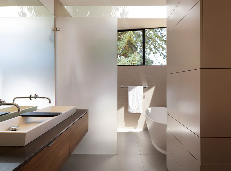 This modern bathroom has a frosted glass frameless shower screen that separates the shower from the vanity. #ModernBathroom