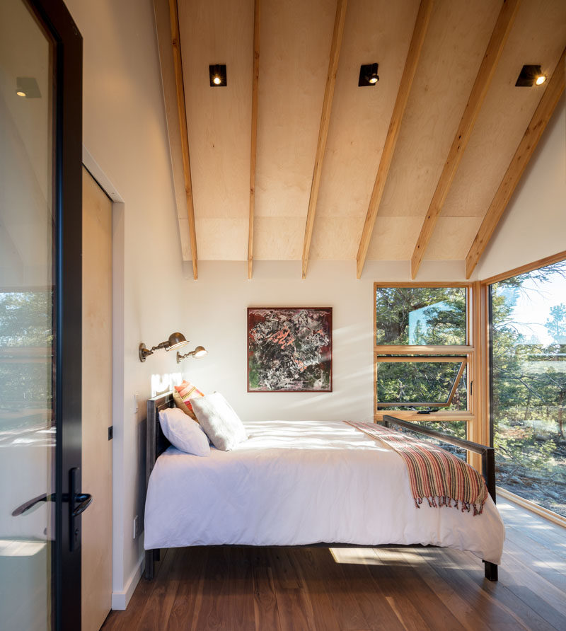 The bedroom in this modern cabin has views of the trees outside. #ModernCabin #Bedroom