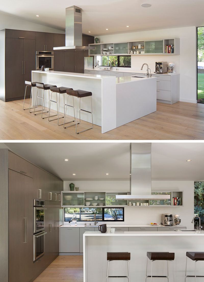 This modern kitchen has plenty of storage and the L-shaped island has a bar area with seating. #KitchenDesign #ModernKitchen