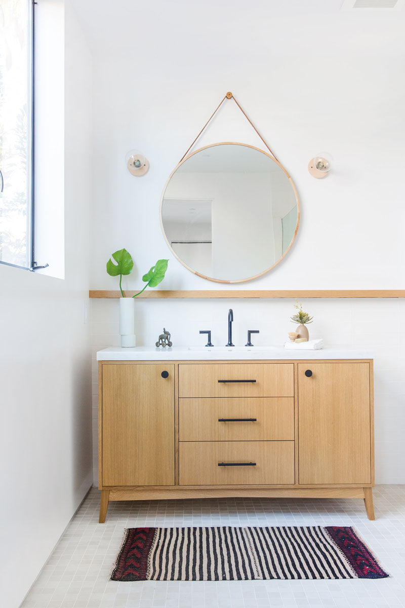 This modern bathroom features a round mirror hanging on the wall, a simple wood shelf and a wood vanity with matte black hardware. #BathroomDesign #ModernBathroom