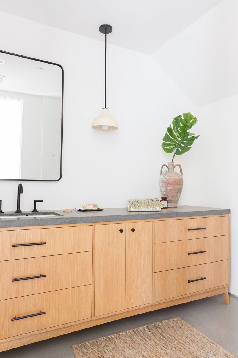 In this modern bathroom, there's a large wood vanity with a concrete countertop and black hardware. #BathroomDesign #WoodAndConcrete