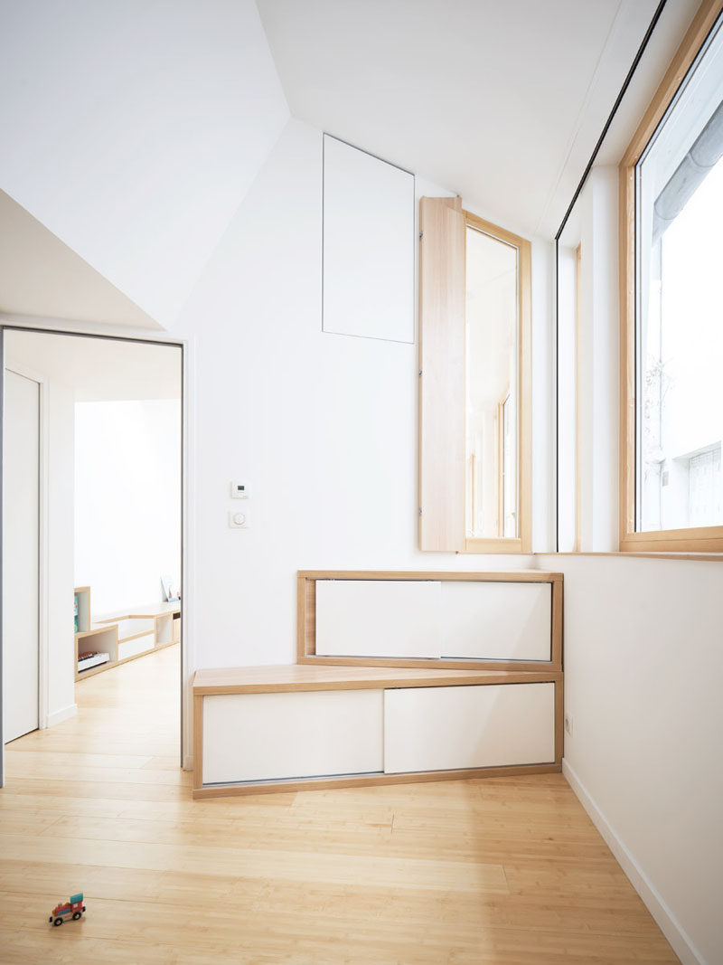 A vertical window provides a view into the kitchen from the bedroom, while below the window, there's storage that neatly fits into the corner. #Storage #Window