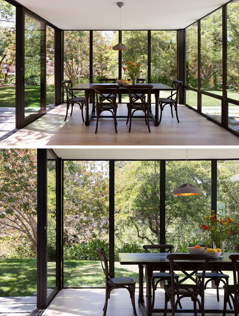 This modern dining room projects into backyard as a glass box surrounded by landscape, creating a space for enjoying time with family and friends and holding impromptu work meetings. #DiningRoom #Windows