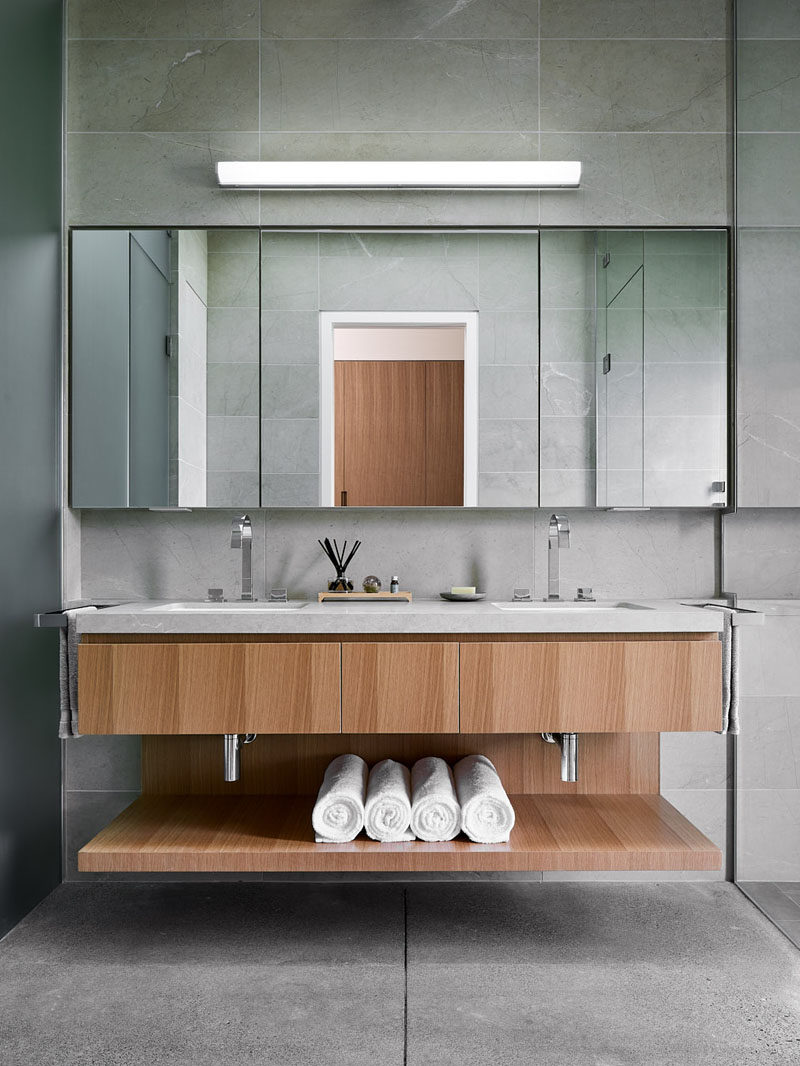 In this modern master bathroom, a double sink vanity with open shelving separates the shower from the toilet. #Vanity #MasterBathroom #BathroomDesign