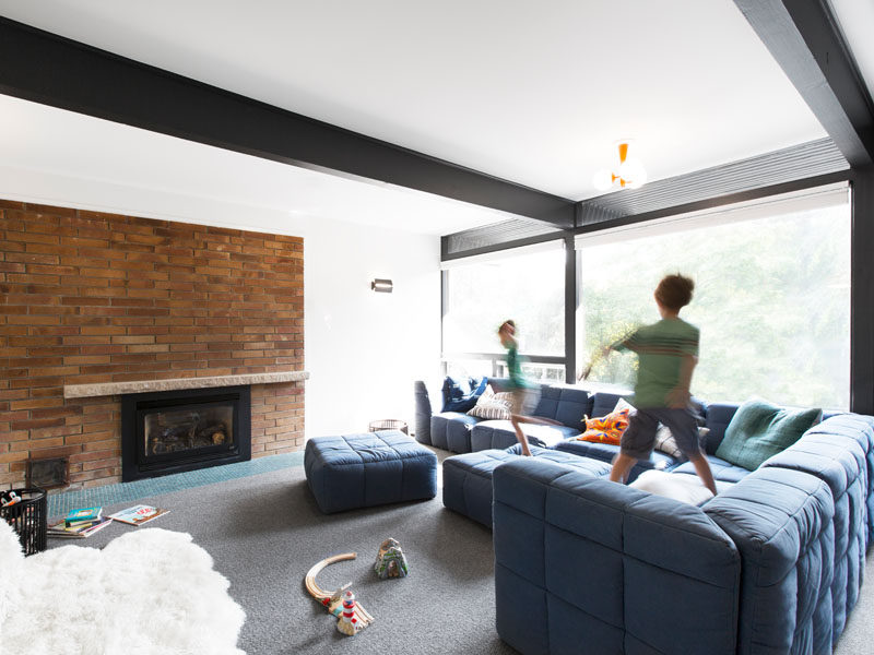 In this media room, a big comfortable blue couch runs alongside the large windows. #MediaRoom #ExposedBlackBeams
